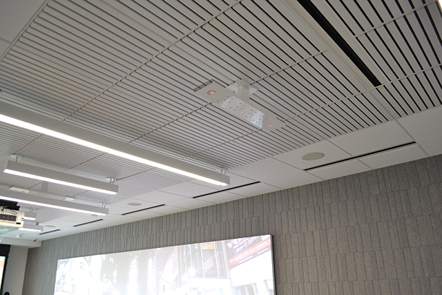 Ceiling-mounted beamforming microphone arrays capture audio in the boardroom.
