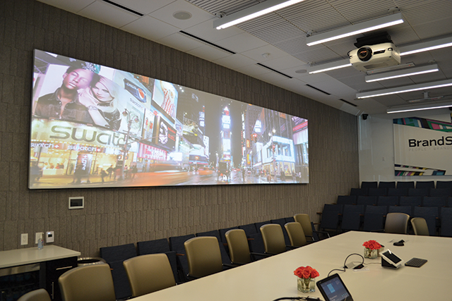 The board room has a custom-built conference table and stadium seating. A three-projector blend is controlled by an iPad.