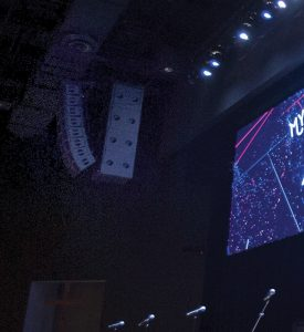 Line arrays with flown subs are hung to the left and right of the LED screen.