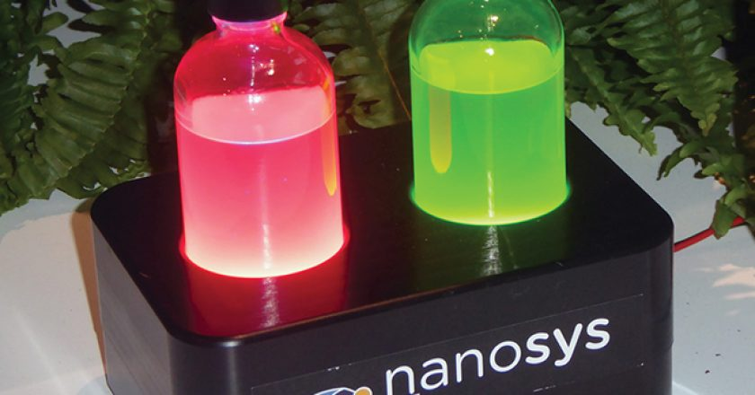 These vials contain red and green quantum dots in liquid suspension, energized by ultraviolet light.