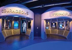 "One of the artifact exhibits in ""A Hero Is…"" features nine interactive exhibits and space program artifacts. Each interactive ""pod"" is self-contained for content and interactivity, and named after a trait that would be required to become one these heroes, such as Courageous, Passionate or Disciplined. When a visitor comes within a 120º cone around one, an IR emitter triggers activation of a 55-inch LCD/LED display mounted in portrait mode, and a 22-inch touchscreen display."