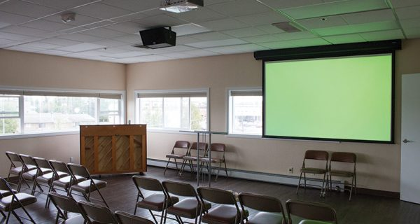 The main sanctuary's projection screen is hung house right. The off-center location of the screen was chosen to counteract the low ceiling height and keep the ceiling speaker out of the projector's beam.