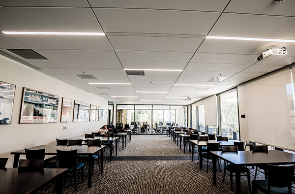 The renovated library has plenty of glass and natural light, which affected projection choices. Projectors that produce 6,500 lumens, like the one seen here, are laser-light-source devices. They replaced the bulb-light source projectors used previously through-out Pepperdine classrooms.