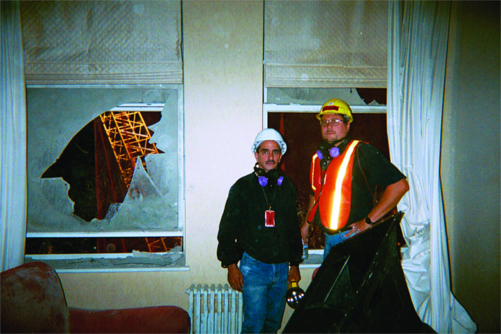 Low Voltage Systems' Al Toledo (left) and Ed Helpeck stand with the stadium horn in a chair at location one, six stories up on Liberty Street, in someone's apartment.