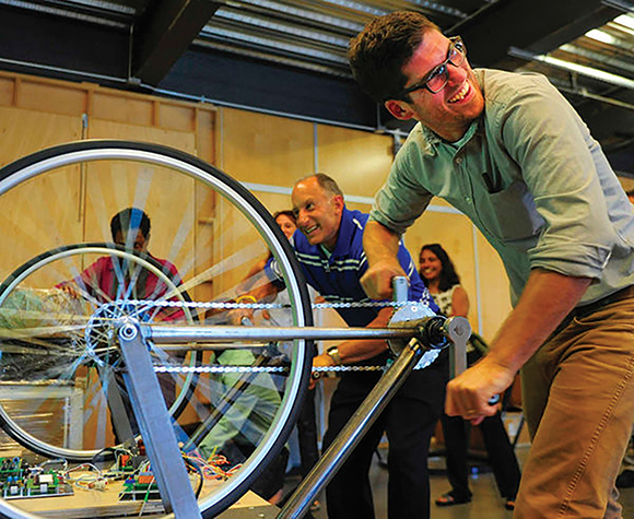 Eric Welch, Prototype Manager, cranks the wheels of a bike at SportsZone Bike Efficiency interactive exhibit, which shows how proper use of gears can improve performance.