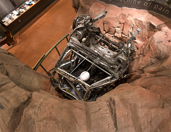 The Crash Pit exhibit lets visitors watch a replay of an iconic crash, sourced from one of four DVD players, on a 32-inch flatpanel monitor nestled just about inside the twisted wreck, while sounds simulating the crash and other audio elements play through a loudspeaker also hidden inside the wreck.