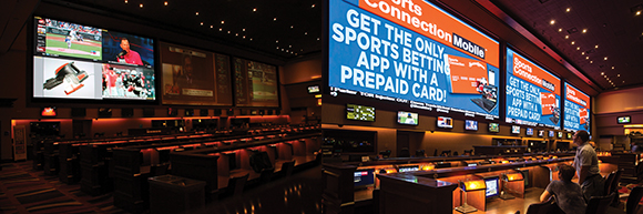 These photos show the difference between the previous installation and new LED video displays. The original setup is on the left. Three large 2.5mm-pitch LED video displays (each one 31½ feet wide by 17 feet tall, totaling more than 1600 square feet of display surface) dominate the sports book, replacing three projection screens that required six high-powered, edge-blended video projectors. Their 3840x2112 native resolution readies the book for 4K and beyond. Integrator H Waldman pointed out that the new videowall screens are only running at 10% to 15% of their maximum brightness capability.