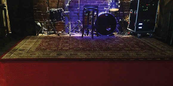 Look closely at the left side of the red stage footer and you'll see a subwoofer nestled underneath, part of the speaker array that was largely dictated by the restaurant's physical layout.