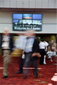 Convention attendees move through the Georgia World Congress Center in Atlanta with a 3x3 videowall made up of 46-inch monitors in the background.