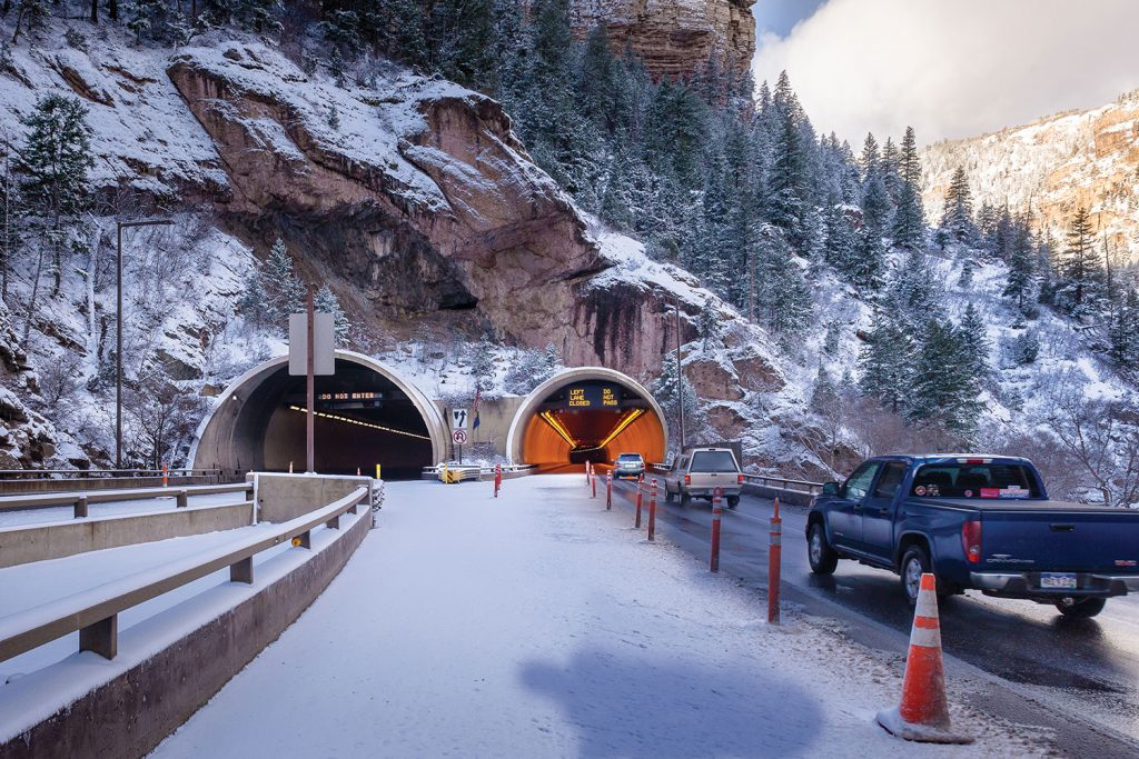 A view of Hanging Lake Tunnels looking to the west. Signs visible here at the bore entry direct traffic and warn drivers of potential hazards ahead. The sign messages are displayed automatically throughout the bores when the operator selects any number of traffic operational modes.