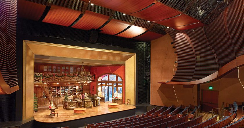 Louvered fascia around the stage's proscenium, up the sides of the seating area and out above the seating area diffuse the sound in the otherwise hard-surfaced, and thus reflective, environment, but also act as screens used to hide the sound system's speakers.