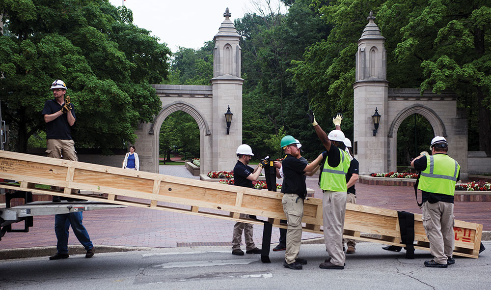 At the historic gates of Indiana University, workers move the long steel beam that was custom built to support the huge videowall.