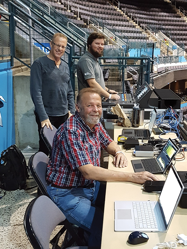 The commissioning team for the new sound system includes Marsh/PMK's David Marsh (left, rear), Ford AV's Brent Kuchero (right, rear) and Marsh/PMK's Jerrold Stevens. The new digital mixing console in its road case can be seen in the background (being operated by Kuchero). This was specified so the sound could be mixed from out in the arena rather than in an enclosed booth.