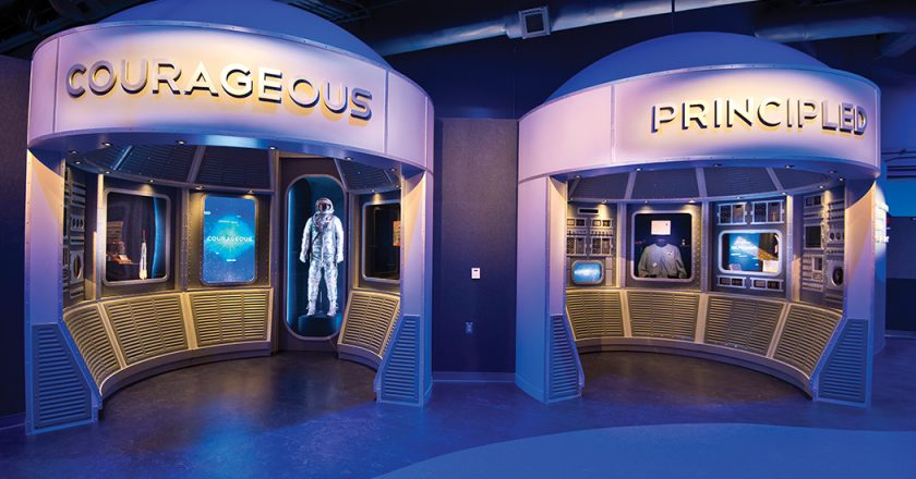 """One of the artifact exhibits in """"A Hero Is…"""" features nine interactive exhibits and space program artifacts. Each interactive """"pod"""" is self-contained for content and interactivity, and named after a trait that would be required to become one these heroes, such as Courageous, Passionate or Disciplined. When a visitor comes within a 120º cone around one, an IR emitter triggers activation of a 55-inch LCD/LED display mounted in portrait mode, and a 22-inch touchscreen display."""