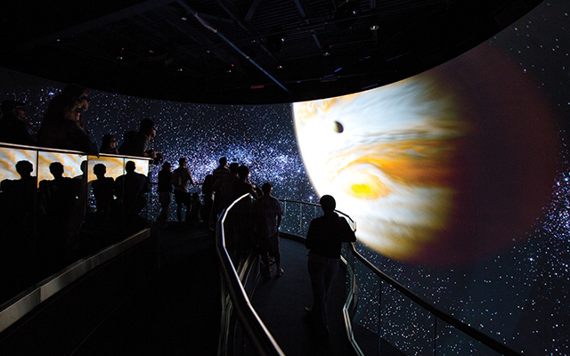 Upon entering and being greeted by a bas-relief of the Mercury 7 astronauts on the façade of the building, visitors ascend a ramp where a seven-minute multimedia presentation unfolds. Two ceiling-mounted projectors display live-action footage on two asymmetrical 16:9 screens.