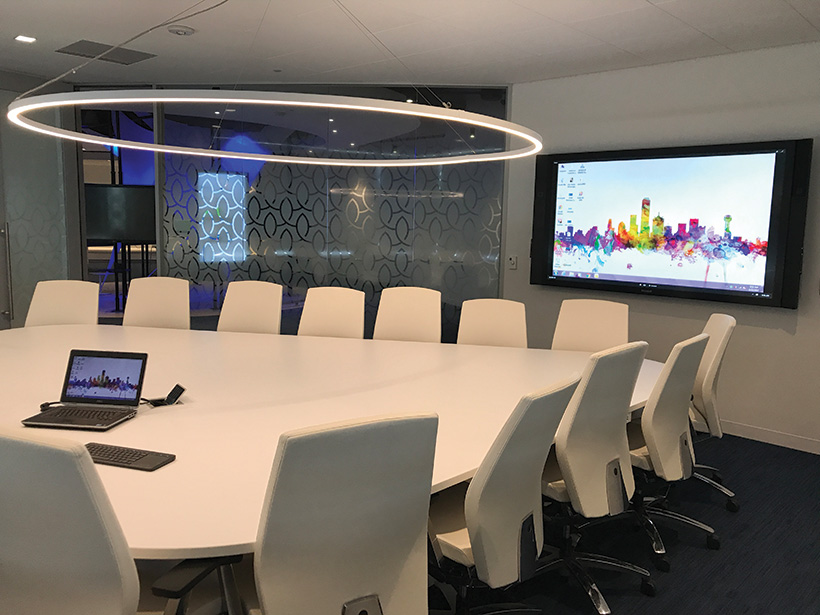 A large conference room, featuring 84-inch display and control system to switch video inputs between table input, wireless connection and inputs from the 32x32 video switcher for the Vignettes, just outside the door.