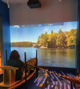 Visitors can take a virtual boat ride at the Adirondack Experience, navigating through a video projection of Blue Mountain Lake.