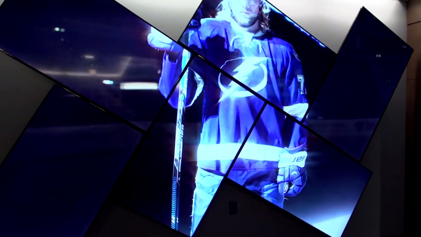A view of the concourse of the NHL's Amalie Arena. A six-foot-tall artistic videowall welcomes attendees with stunning, eye- catching footage of the team's glories.