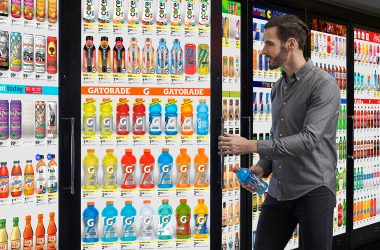 man grabbing beverage from refrigerator with a digital screen